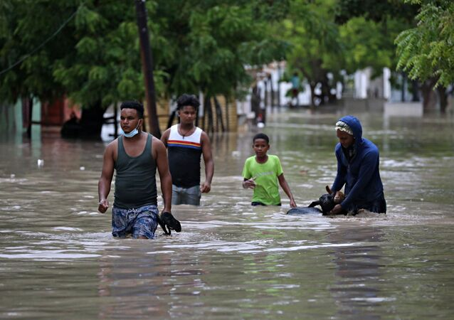 People move their animals through the floods caused by the passage of Storm Laura in Azua, Dominican Republic August 23, 2020.
