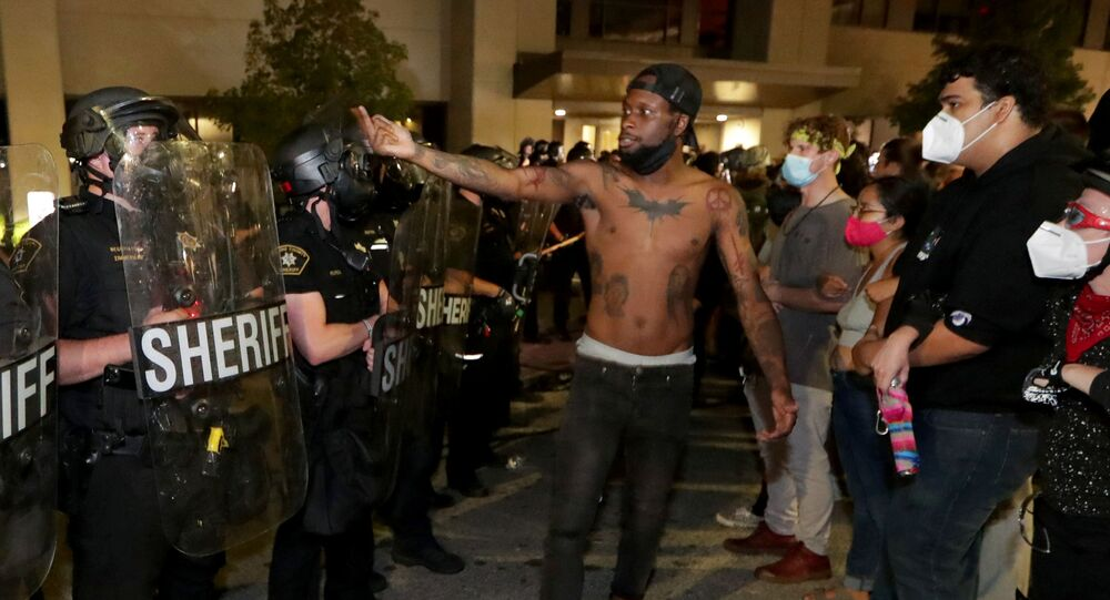 A man confronts police outside the Kenosha Police Department in Kenosha, Wisconsin, U.S., during protests following the police shooting of Black man Jacob Blake August 23, 2020.