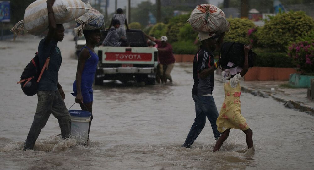 People cross a flooded street during the passage of Tropical Storm Laura, in Port-au-Prince, Haiti August 23, 2020.