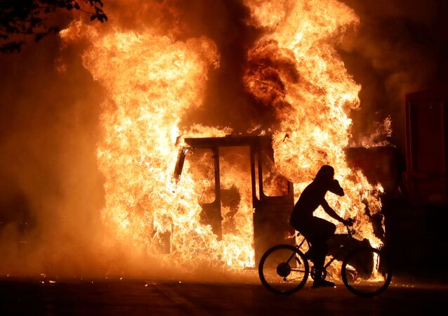 A man on a bike rides past a city truck on fire outside the Kenosha County Courthouse in Kenosha, Wisconsin, U.S., during protests following the police shooting of Black man Jacob Blake August 23, 2020.