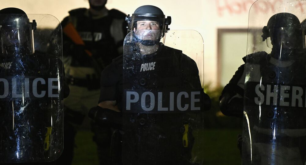 Police and members of the Sheriff's department hold a perimeter, during a protest after a Black man identified as Jacob Blake was shot several times by police last night, outside the Kenosha County Courthouse in Kenosha, Wisconsin, U.S. August 24, 2020