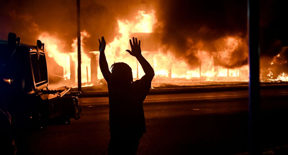 A man walks by an armoured vehicle as B&L Office Furniture burns in the background as protests turn to fires after a Black man, identified as Jacob Blake, was shot several times by police last night in Kenosha, Wisconsin, U.S. August 24, 2020