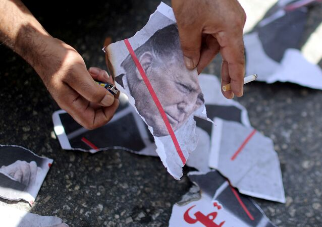 A Palestinian demonstrator burns a picture depicting U.S. President Donald Trump during a protest against the United Arab Emirates' deal with Israel to normalise relations, in Gaza City August 19, 2020