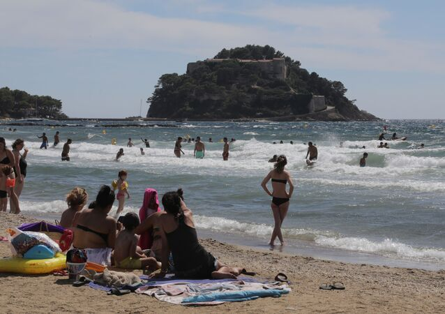 People sunbathe on the beach of Bregancon fort, the French presidential summer residence, where French President Emmanuel Macron stays for holidays in Bormes-les-Mimosas, August 17, 2020