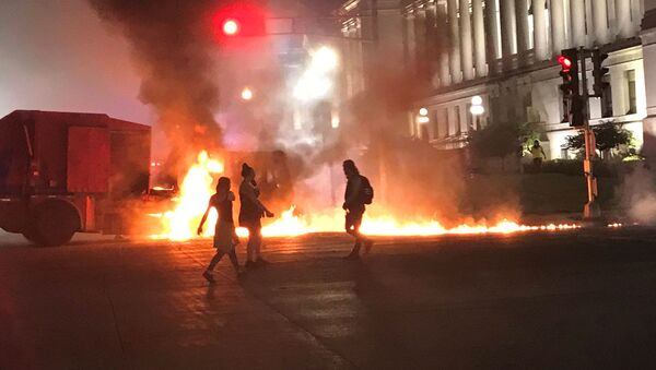 People stand near a burning vehicle in front of the Kenosha County couthouse in Kenosha, Wisconsin, U.S., during protests following the police shooting of Black man Jacob Blake in this August 24, 2020 picture obtained from social media - Sputnik International