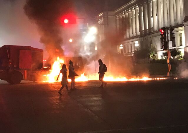 People stand near a burning vehicle in front of the Kenosha County couthouse in Kenosha, Wisconsin, U.S., during protests following the police shooting of Black man Jacob Blake in this August 24, 2020 picture obtained from social media