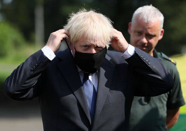 Britain's Prime Minister Boris Johnson puts on a mask at the Northern Ireland Ambulance Service HQ during his visit to Belfast, Northern Ireland August 13, 2020.