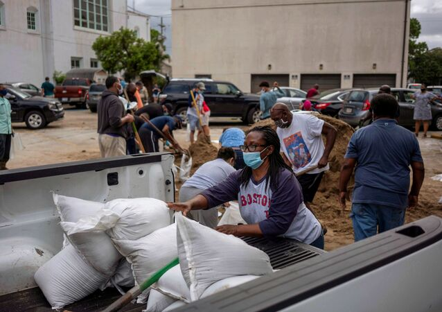 A woman puts sandbags on a cart as residents fill sandbags at St. Raymond Church, provided by Mayor LaToya Cantrell and the local government, as Hurricane Laura warnings have been issued for part of Louisiana and Texas, in New Orleans, Louisiana, U.S., August 25, 2020.