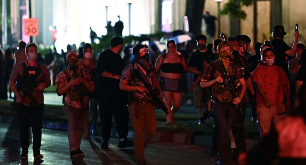 Men carry rifles as people protest outside the Kenosha County Courthouse after a Black man, identified as Jacob Blake, was shot several times by police in Kenosha, Wisconsin, U.S. August 25, 2020. Picture taken August 25, 2020