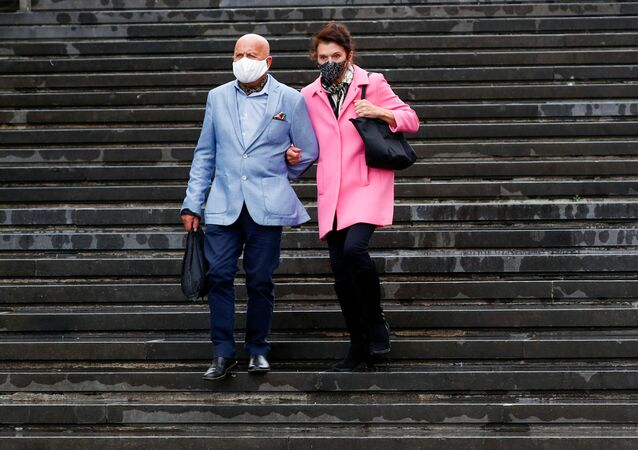 A couple wearing protective face masks walk down the stairs amid the coronavirus disease (COVID-19) outbreak in Brussels, Belgium August 25, 2020. Picture taken August 25, 2020.