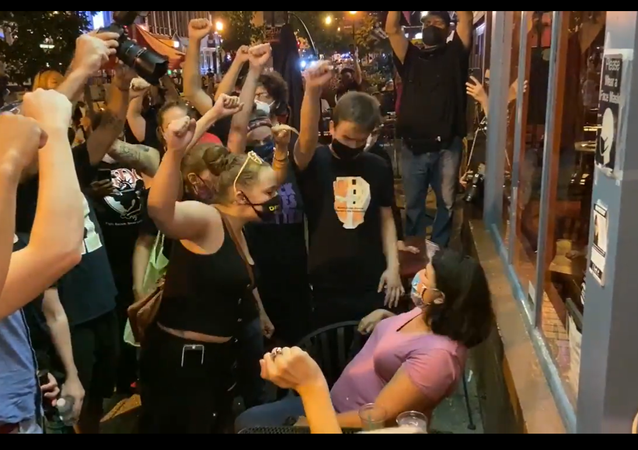 A screenshot from a video showing BLM protestors confronting diners outside a DC restaurant