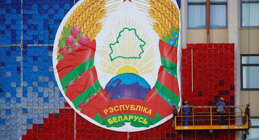 Workers mount a huge banner with the national emblem of Belarus on a facade of the Maxim Tank Belarusian State Pedagogical University at the Independence Square in Minsk, Belarus August 24, 2020