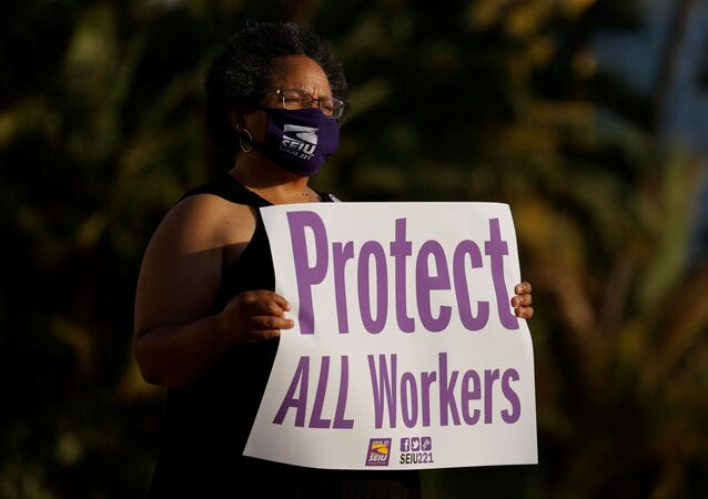 Social Worker Iris Trammel hold a sign during a vigil to honor San Diego county employees who have lost their lives to the coronavirus (COVID-19) while working the frontline of the pandemic in San Diego, California August 24, 2020