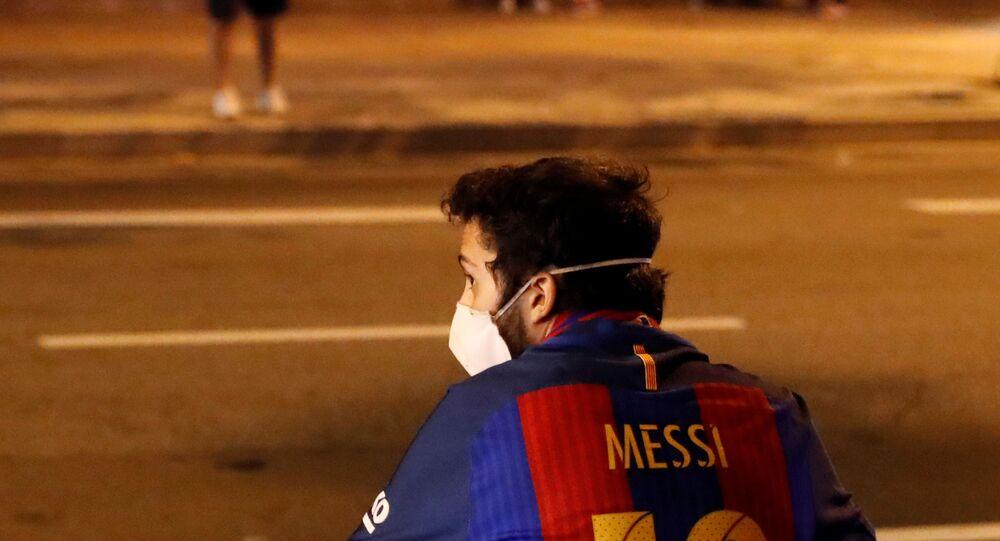 A Barcelona fan sitting on the sidewalk