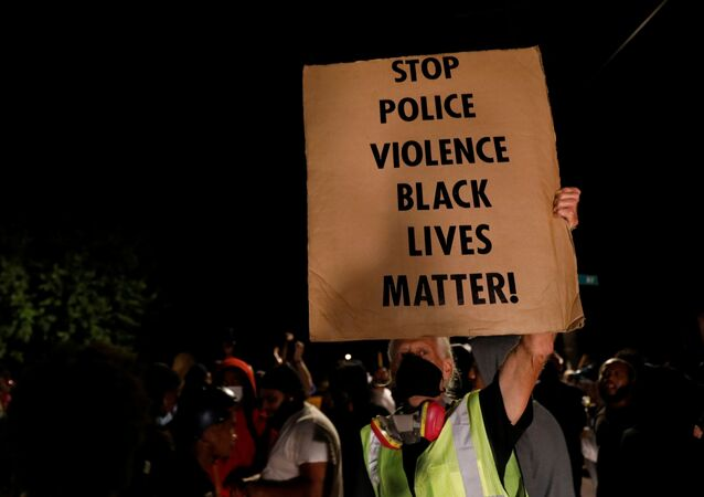 A man holds up a sign as demonstrators take part in a protest following the police shooting of Jacob Blake, a Black man, in Kenosha, Wisconsin, U.S. August 26, 2020.