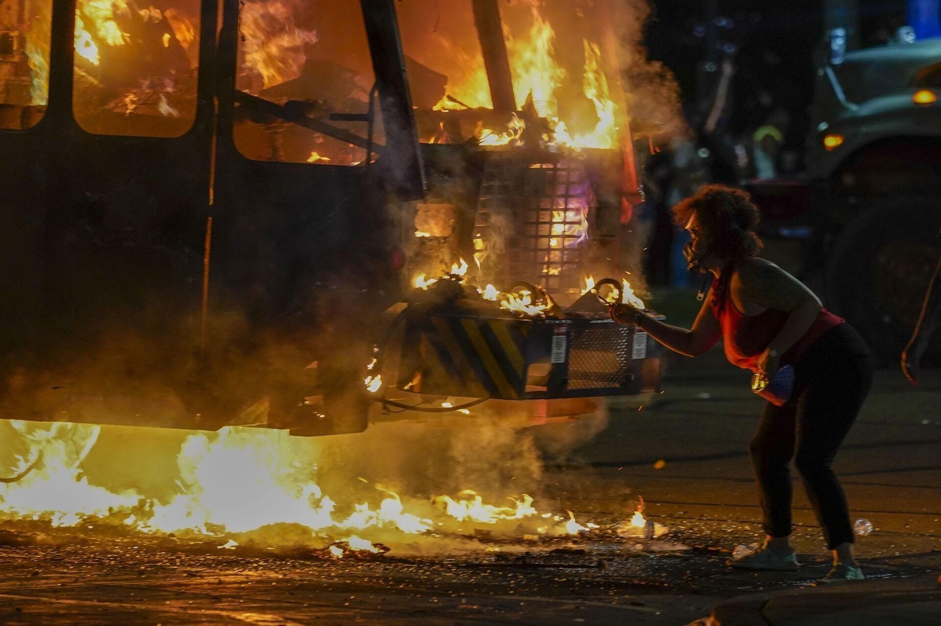 A protester lights a cigarette on a garbage truck that was set on fire during protests late Monday, Aug. 24, 2020, in Kenosha, Wis., sparked by the shooting of Jacob Blake by a Kenosha Police officer a day earlier.  - Sputnik International, 1920, 07.09.2021