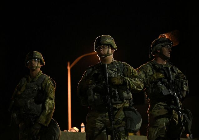 Members of the Wisconsin National Guard keep watch at their post behind the Kenosha Police Department building following the police shooting of Jacob Blake, a Black man, in Kenosha, Wisconsin, U.S., August 27, 2020.