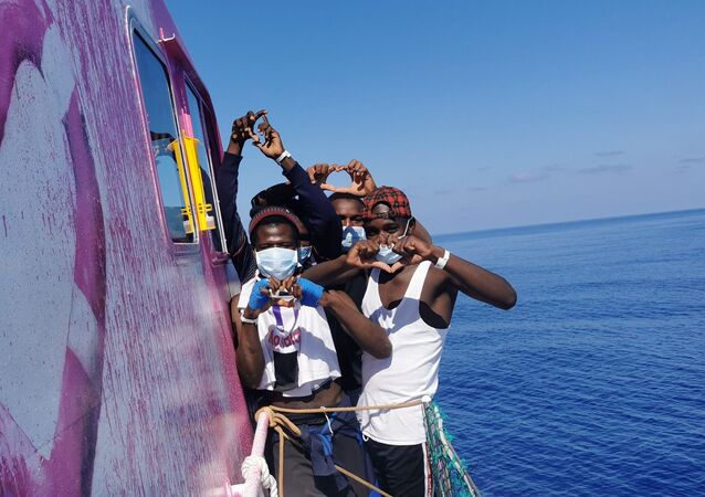 In this undated handout photo people pose for a photo after being rescued by the Louise Michel, a migrants search and rescue ship operating in the Mediterranean and financed by British street artist Banksy, at sea.