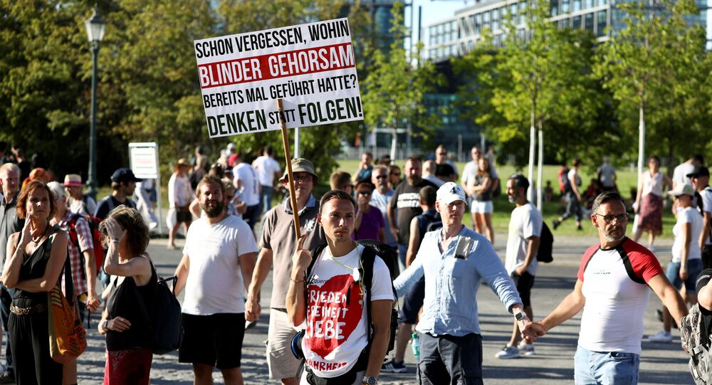 Germans take part in a protest against the government's restrictions imposed over the coronavirus outtbreak, in Berlin, Germany, 1 August 2020.