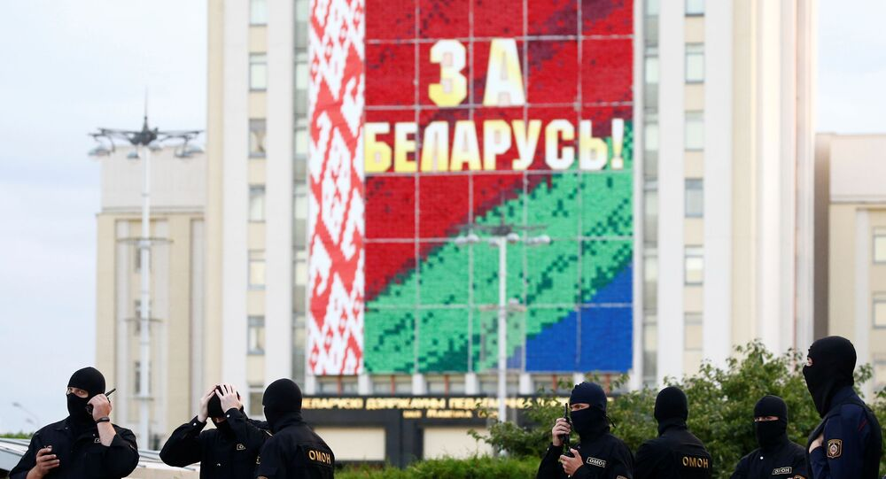 Law enforcement officers are seen during an opposition demonstration against presidential election results at the Independence Square in Minsk, Belarus August 28, 2020. The banner on the building reads: For Belarus!