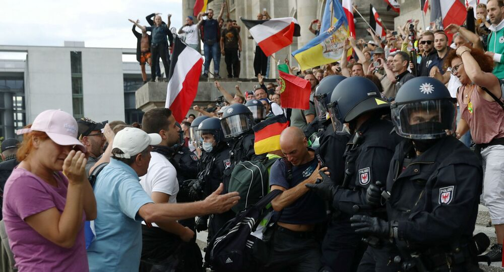 Police officers scuffle with a protester in front of the Reichstag Building