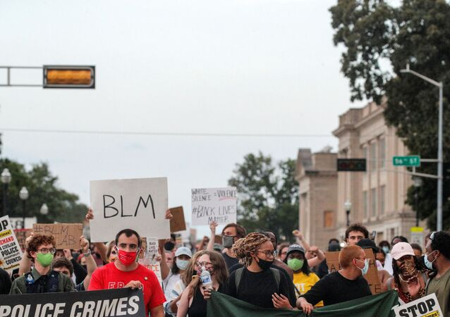 People march with signs, following the police shooting of Jacob Blake, a Black man, in Kenosha