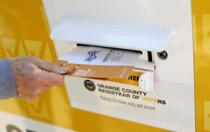 A voter drops ballots for the 3 March Super Tuesday primary into a mobile voting mail box in Laguna Woods, California, US, 24 February 2020.