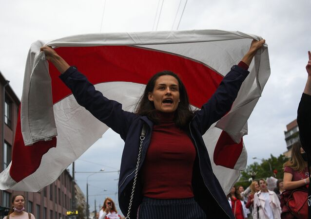 A woman carries a white-red-white flag during a rally against police violence, in Minsk, Belarus. Up to 1,000 protesters, most of them women, gathered in the center of the Belarusian capital on Saturday to protest against police violence during anti-government rallies throughout the country.