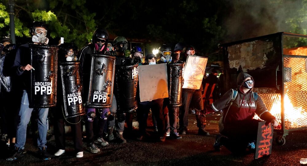 Demonstrators confront police (not pictured) during a protest against police violence and racial injustice in Portland, Oregon, 23 August 2020