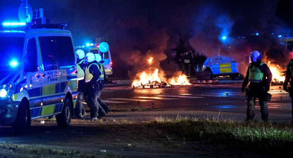 Police officers walk near the burning tyres and pallets during a riot in the Rosengard neighbourhood of Malmo, Sweden August 28, 2020