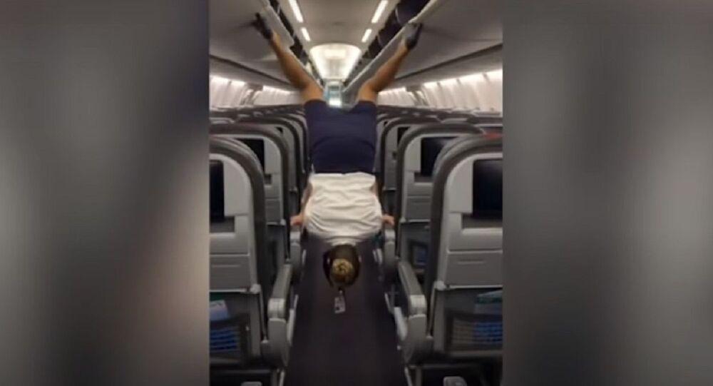 Flight attendant flips upside down to close overhead bins