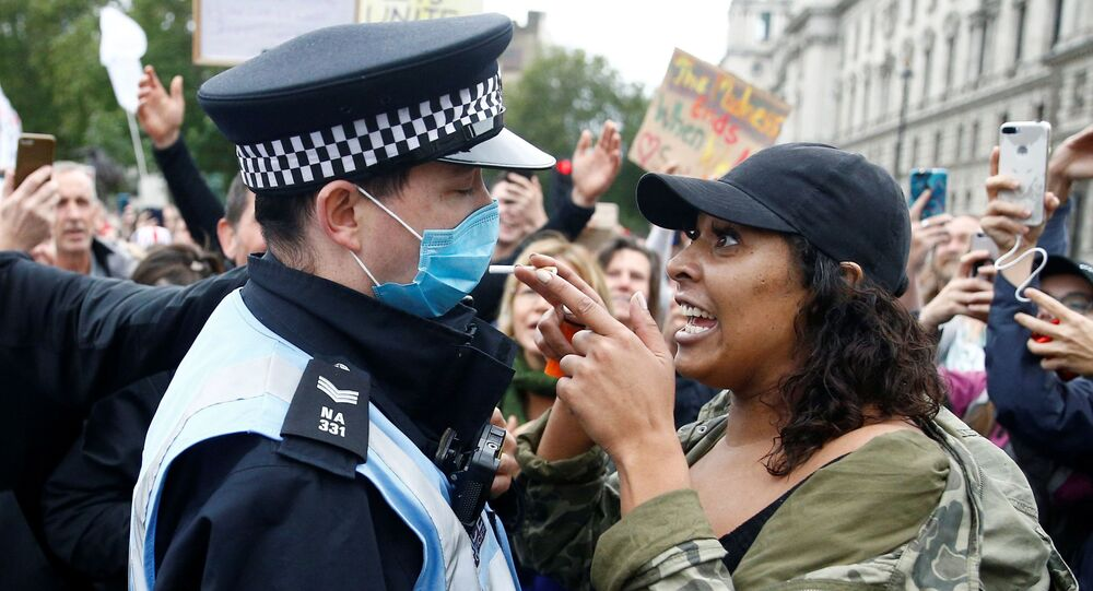 A protester sings and gestures towards a police officer during a demonstration against the lockdown and use of face masks, amid the coronavirus disease (COVID-19) outbreak, outside Downing Street in London, Britain, August 29, 2020