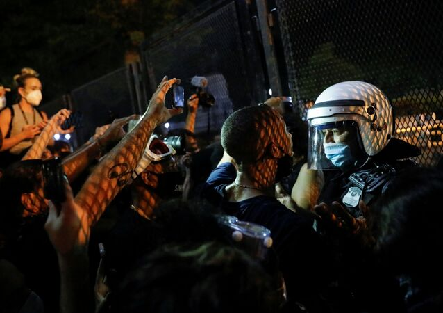 Demonstrators face off with a security officer near a fence around the White House during a protest  in Washington, U.S. August 27, 2020