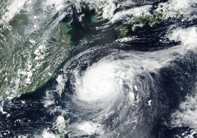 This Monday, Aug. 31, 2020, satellite image released by NASA shows Typhoon Maysak over Japan's southernmost islands, including Okinawa, center. The powerful typhoon was blowing over Japan's southernmost islands early Tuesday on course for Japan's main southern island and later the Korean Peninsula. Warnings issued for the area around Okinawa, home to U.S. military bases, said strong gusts could cause some homes to collapse and extremely high tides were a risk as well.