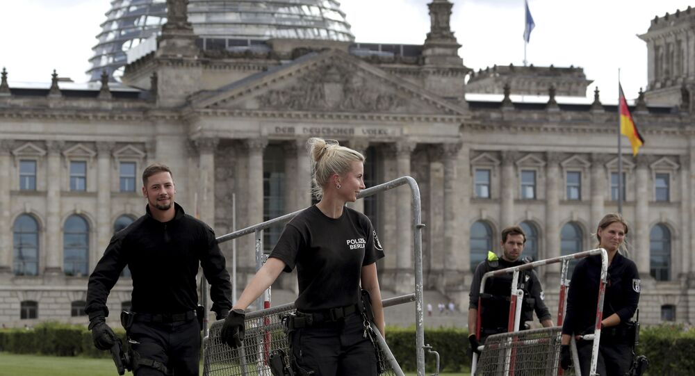 Police officers carry crowd control barriers in front of the Reichstag building, home of the German federal parliament (Bundestag), in Berlin, Germany, Monday, 31 August 2020.