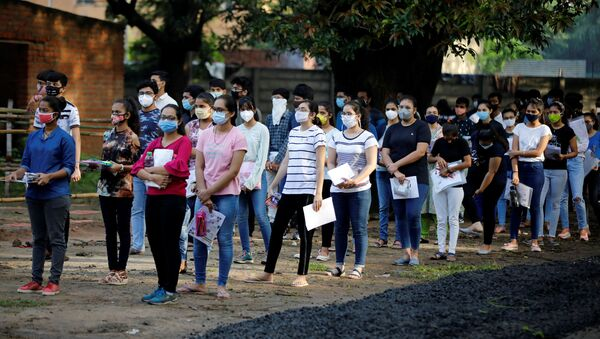 Students wearing protective face masks wait to enter an examination centre for Joint Entrance Examination (JEE), amidst the spread of the coronavirus disease (COVID-19), in Ahmedabad, India, September 1, 2020 - Sputnik International