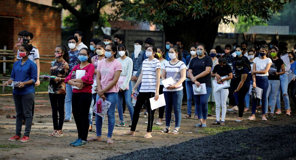 Students wearing protective face masks wait to enter an examination centre for Joint Entrance Examination (JEE), amidst the spread of the coronavirus disease (COVID-19), in Ahmedabad, India, September 1, 2020