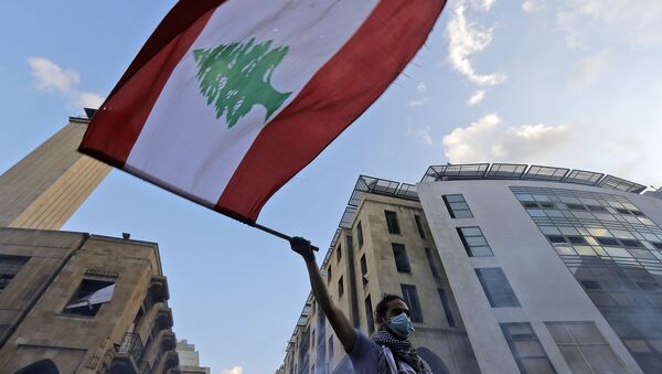 A Lebanese protester waves a national flag amid clashes with security forces in central Beirut on August 10, 2020.  - Sputnik International