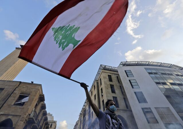 A Lebanese protester waves a national flag amid clashes with security forces in central Beirut on August 10, 2020.