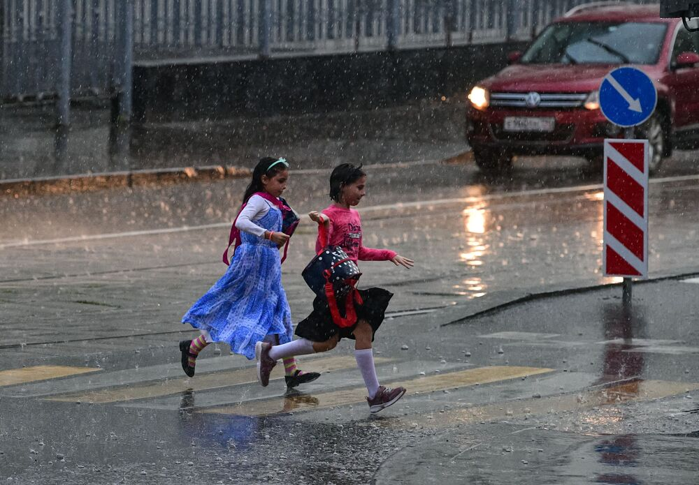 Girls run across the road during the rain in Moscow.