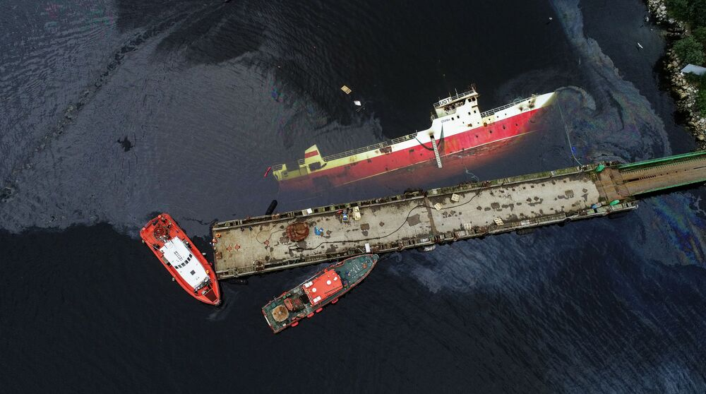 Cleaning up for oil spilled from the Saida vessel which capsized following a fire in Murmansk