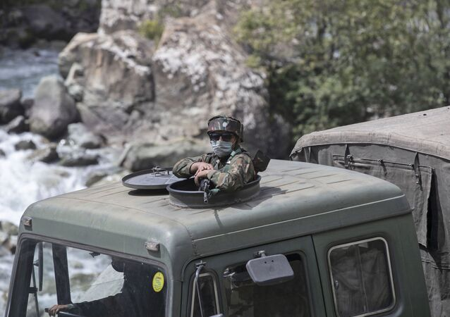 An Indian army soldier keeps guard on top of his vehicle as their convoy moves along the Srinagar-Ladakh highway at Gagangeer, northeast of Srinagar, in Indian-controlled Kashmir, Tuesday, 1 September 2020.