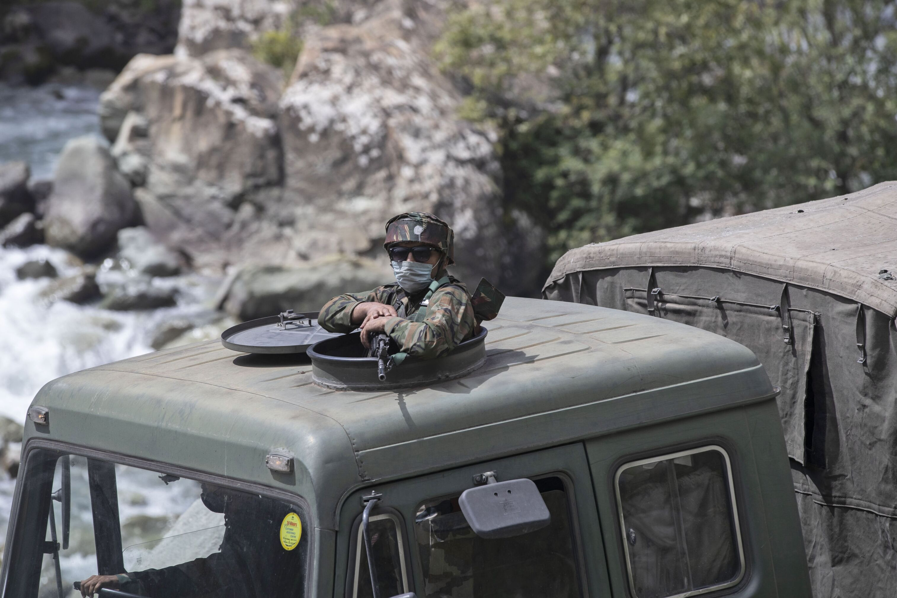 An Indian army soldier keeps guard on top of his vehicle as their convoy moves on the Srinagar- Ladakh highway at Gagangeer, northeast of Srinagar, Indian-controlled Kashmir, Tuesday, Sept. 1, 2020