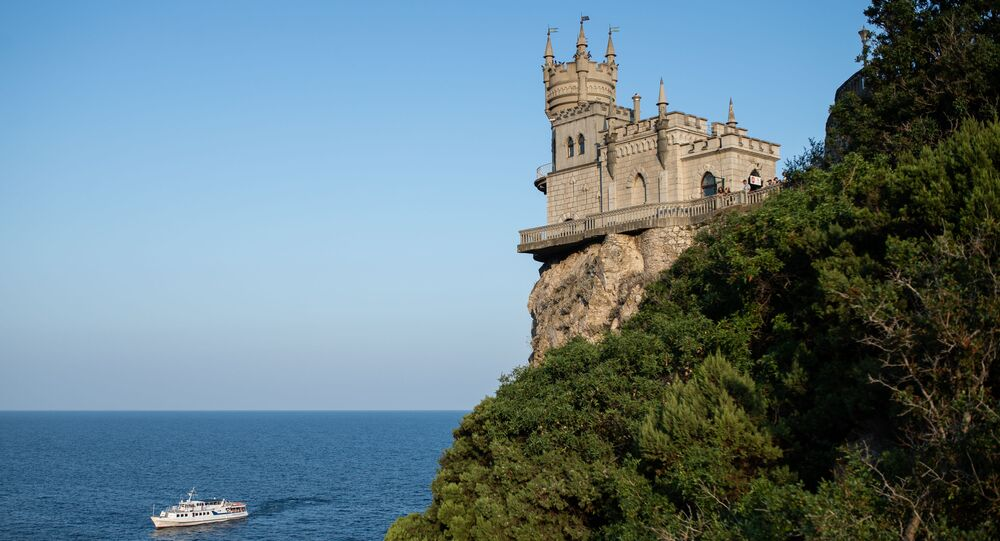 A vessel passes the Swallow's Nest castle overlooking the Black Sea outside Yalta, Crimea, Russia