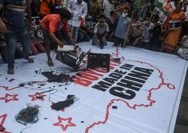 Congress party supporters leave Chinese goods on a flag displaying the country and flag of China along with an inscription reading 'Boycott Made in China' before burning them during an anti-China demonstration in Kolkata on Juane 18, 2020