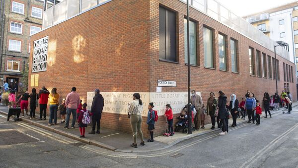 Pupils and parents queue on the first day back to school at Charles Dickens Primary School in London, Tuesday Sept. 1, 2020. Hundreds of thousands of British schoolchildren are heading back to classrooms, with the country watching nervously to see if reopening schools brings a surge in coronavirus infections. Tuesday marks the start of term for about 40% of schools in England and Wales, with the rest reopening in the coming days.  - Sputnik International