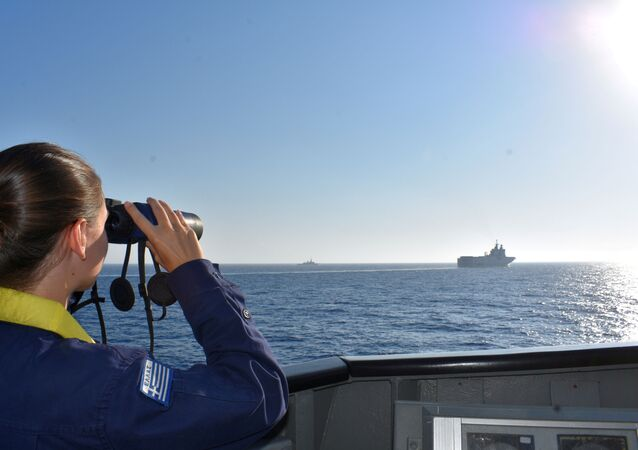 A woman looks through binoculars as Greek and French vessels sail in formation during a joint military exercise in Mediterranean sea, in this undated handout image