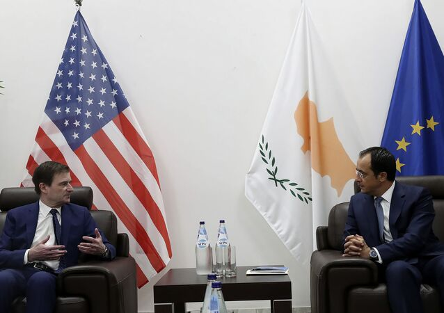 Cyprus' foreign minister Nikos Christodoulides, right, talks with Under Secretary of the United States of America, for Political Affairs, David Hale during their meeting at Larnaca international airport, Cyprus, Sunday, Aug. 16, 2020. Hale's brief stop in Cyprus comes amid heightened tensions over Turkey's hydrocarbons search in waters Greece and Cyprus claim as their own.