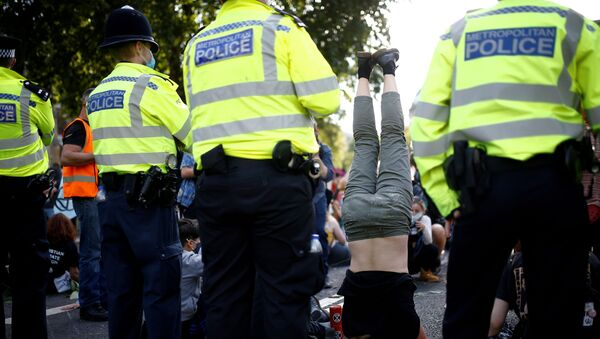 An Extinction Rebellion climate activist stands on their head during a peaceful disruption of British Parliament as lawmakers return from the summer recess, in London, Britain September 1, 2020. - Sputnik International