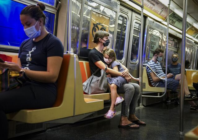 A child rests on a subway car while riders wear protective masks due to COVID-19 concerns, Monday, Aug. 17, 2020, in New York.